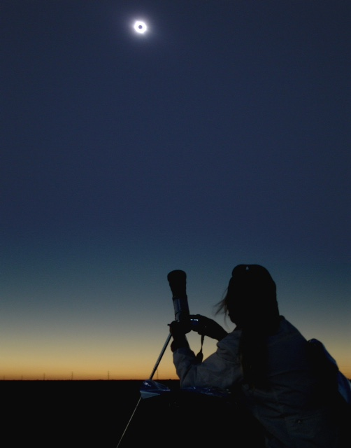 A woman watches a total solar eclipse.
