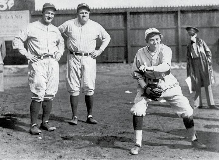 Jackie Mitchell pitches while Lou Gehrig (far left) and Babe Ruth (middle left) look on. Photo courtesy of the Library of Congress.