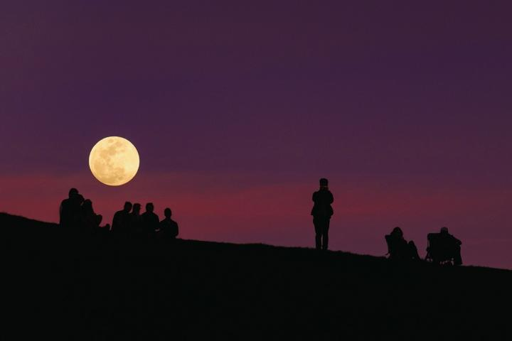 Harvest moon with people standing in front