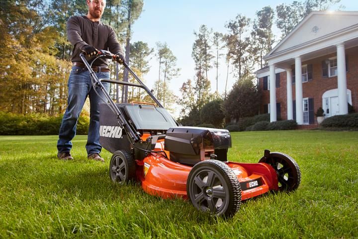Image: Cutting the grass with an electric cordless lawn mower.
